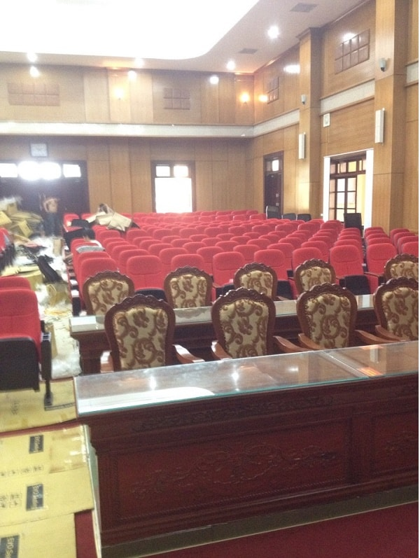 Không gian hội trường có điểm nhấn là hai hàng ghế và bàn ở trên cùng